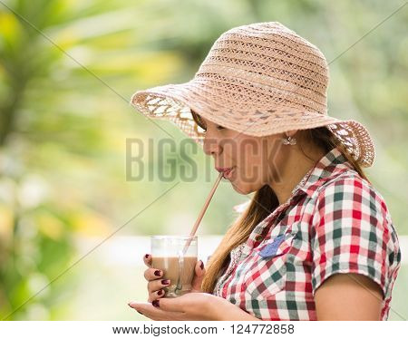 Young woman in square pattern shirt enjoying a coffee oudoors garden environment.