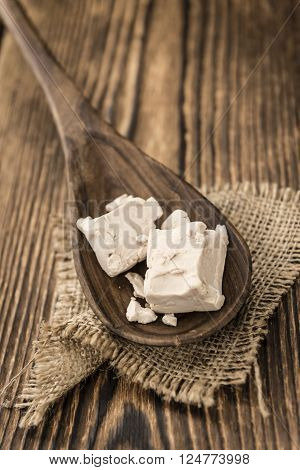 Heap of Yeast (selectivce focus) on wooden background (close-up shot)