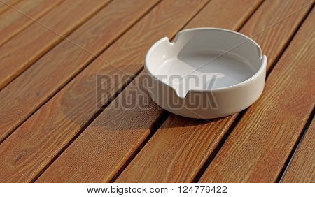 empty white ashtray on a wooden table
