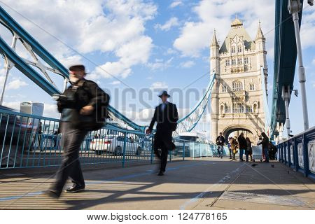 LONDON, UK -?? APRIL 05 2016: Motion blurred commuters crossing Tower Bridge during rush hour. Tower Bridge links the South of River Thames to the City area.
