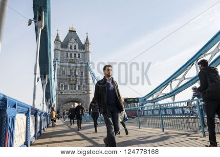 LONDON, UK -?? APRIL 01 2016: Commuters crossing Tower Bridge during rush hour. Tower Bridge links the South of River Thames to the City area.