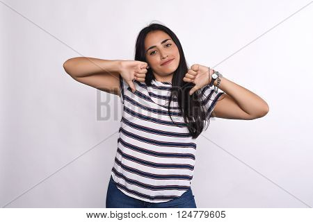 Attractive young latin woman with her fingers down. Isolated white background.