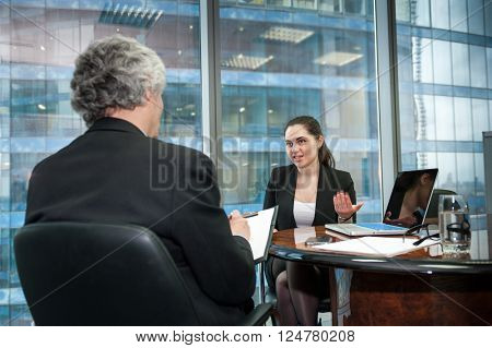 Boss interviews young employee in modern office