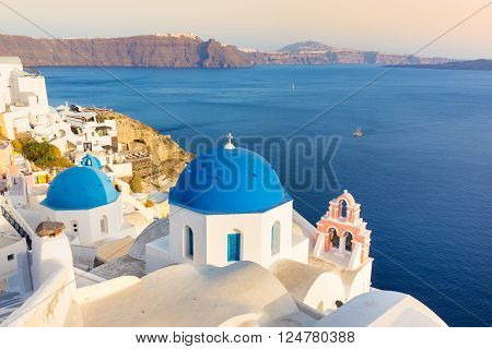 World famous traditional whitewashed chuches and houses of Oia village on Santorini island, Greece. Sunset light.