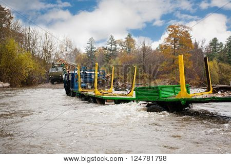 Heavy-duty truck for transportation of logs stuck in the river. Autumn rain. Russian Far East.