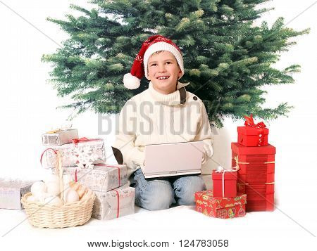 A boy is siting with cristmas gifts and notebook