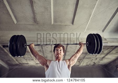 Low angle shot of a strong young man lifting heavy weigths above his head with a determined expression