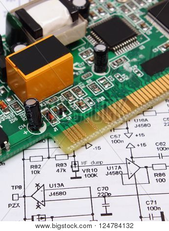 Printed circuit board with electrical components lying on construction drawing of electronics drawings for engineer jobs technology
