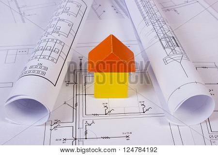 House shape made of wooden blocks and rolls of diagrams lying on electrical construction drawings of house, concept of building house, drawing for projects