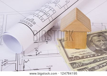 House shape made of wooden blocks and currencies dollar lying on electrical construction drawings of house concept of building house drawing for projects