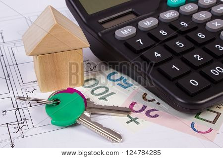 House shape made of wooden blocks home keys polish currency money and calculator on electrical construction drawings of house calculation of cost building house