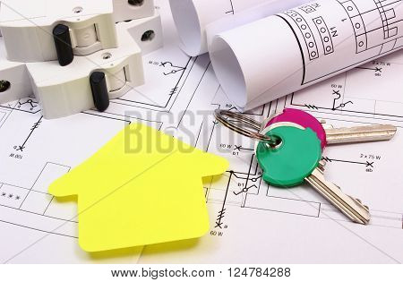 House of yellow paper, home keys, rolls of diagrams and electric fuse lying on construction drawing of house, technology and concept of building home