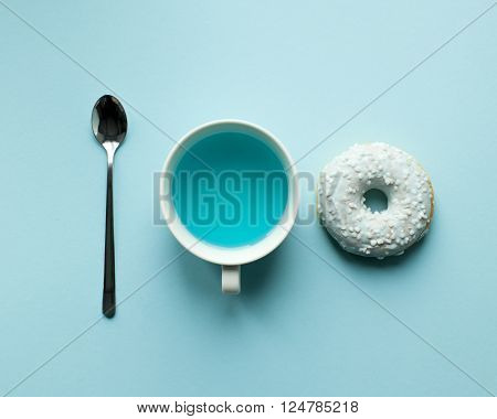 Turquoise donut, spoon and tea on blue background. Art food
