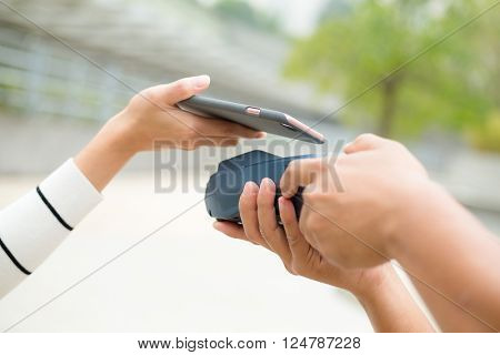 Woman use mobile phone on pos machine