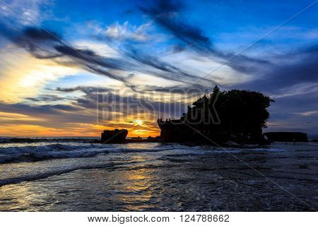 Silhouette of Tahah Lot Temple and ocean waves at sunset, Bali, Indonesia