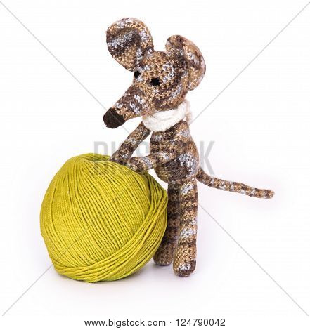 small colorful knitted toy mouse in a white scarf playing with colored yarn, threads of wool, Bright children's toy, clew