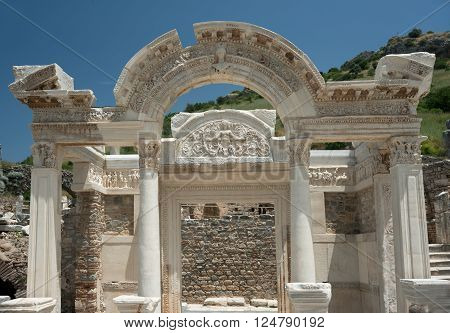 Marble high decorated portal in ancient town Ephesus. Clear blue sky in background.