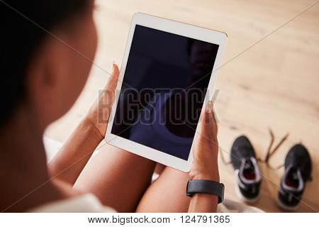 Young black woman using tablet computer, over-shoulder view