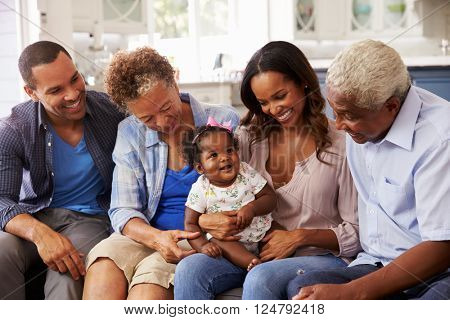 Grandparents, parents and a happy baby girl on mumâ??s knee