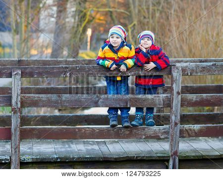 Two funny little kid sibling boys and friends in colorful clothes standing on bridge on spring day. Children having fun together, autumn or winter. Happy, joyful family