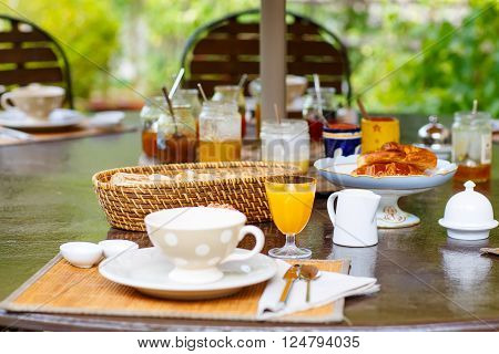 Table laid for breakfast outside in summer with various jams, bread, coffee, croissants, muesli and orange juice. French breakfast. Provence, France