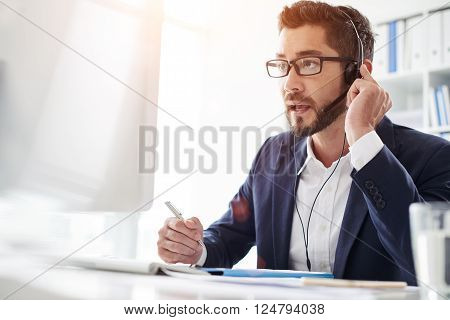 Tech support manager in headset consulting a client