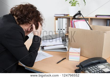 Fired employee holding her head in desperation with her box on the desk