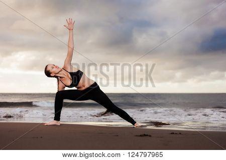 Summer sunrise yoga session on beautiful Playa de La Tejita beach with view on atlantic ocean and Punta Roja rock - tropical Tenerife island, Canary in Spain. Triangle pose - trikonasana
