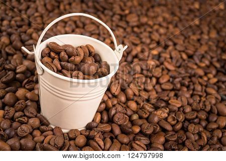 Coffee Bucket Concept. Small Metal Bucket with Coffee Beans on Aged Wood Table.