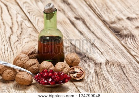 Tincture or juice of Pomegranate and ripe red seeds in an iron spoon on old wooden textured table