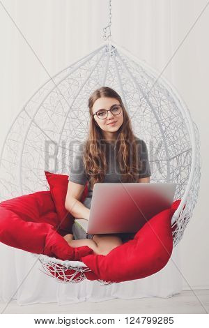 Young beautiful woman in eyeglasses in fashionable armchair with laptop. Girl with pc in modern interior at red cushions. Stylish high key portrait of freelancer, work at home concept. Soft toning. ** Note: Visible grain at 100%, best at smaller sizes