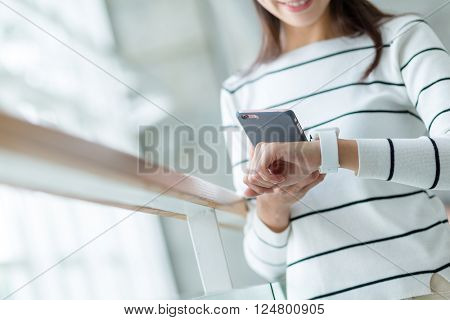 Woman connecting smart watch and cellphone