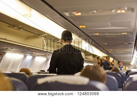 Interior of airplane with passengers and stewardess walking the aisle.