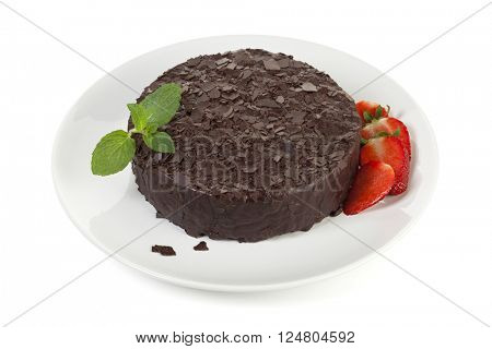 Whole chocolate cake garnished with strawberries an mint leaves on plate, isolated on white background