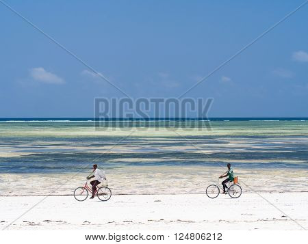 PAJE, ZANZIBAR - MARCH 30, 2016: Local people biking on the beach in Zanzibar, Tanzania.