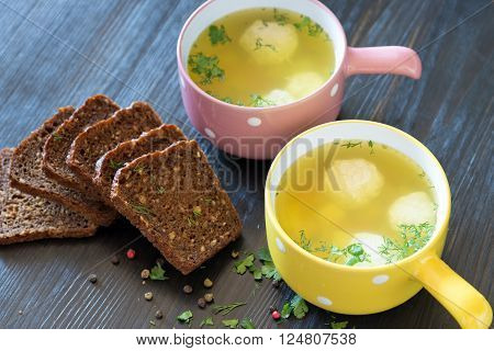 soup with meatballs in colorful bowl with slices of grain bread