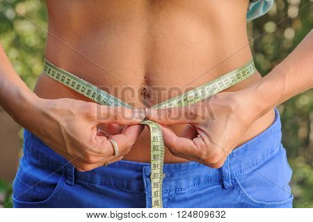 Slim woman measures her bare waistline with a measuring tape. She is outdoors