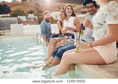 Shot of young people drinking cocktails the swimming pool. Friends sitting on the edge of the pool with feet in water. Relaxing by the pool with drinks. They are enjoying a party.