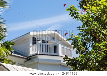 Veranda on white house with tropical flowers