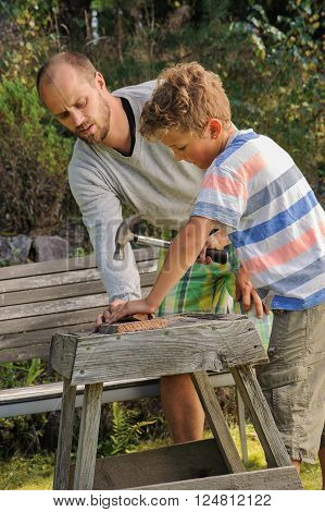 Father teaches son how to hammer a nail. He worries about getting his fingers hit. They're outdoors.