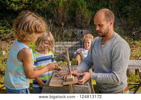 Father shows his 3 sons how to make a sailing boat from pieces of wood. He teaches the boys how to hammer a nail. They're outdoors