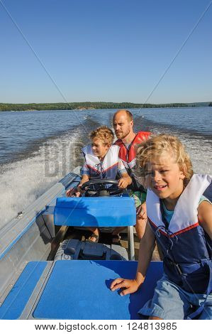 Father and sons out boating together. The father lets one of the boys steer the boat. They're wearing life vests. In the background there's forested shore line water and blue sky.