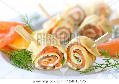Rolls of thin pancakes with smoked salmon, horseradish cream cheese and rocket leaves