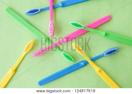 Tooth brushes on bright neon colors on green