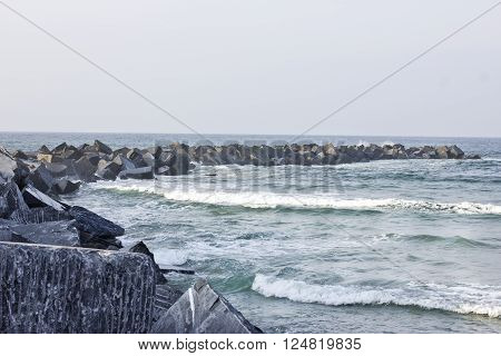 Rounded shape breakwater built with huge square stones
