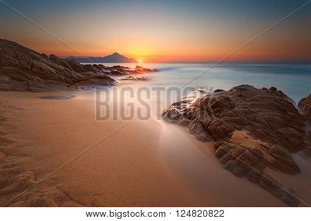 Beautiful sunrise on Greek coast of Aegean sea with holy mountain Athos in background. Long exposure shot with motion blur effect. Chalkidiki Greece.