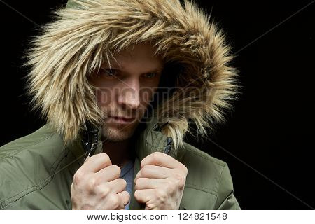 Low key studio portrait of young adult caucasian model wearing winter coat with hood on. Isolated on black.