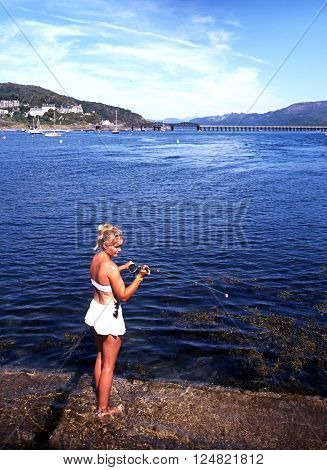 BARMOUTH, UK - AUGUST 6, 1995 - Woman fishing from the quay with views towards the railway bridge Barmouth Gwyedd Wales UK Western Europe, August 6, 1995.