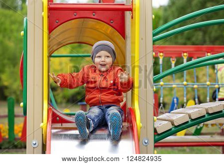 Blonde baby boy sits on a childrens slide at the playground, summer outdoors