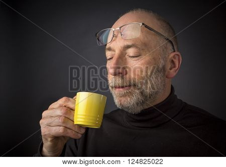 Enjoying morning espresso coffee - 60 years old  man with a beard and glasses - a headshot against a black background